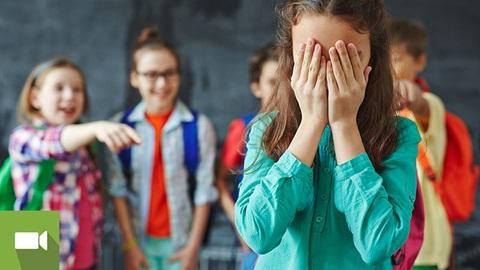 rapariga com as mãos na cara a ser vítima de bullying