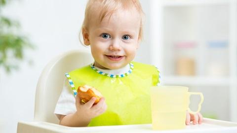 Uma bebé loira e sorridente, vestida com uma t-shirt branca e um babete amarelo e verde, agarra um pão. Está sentada numa cadeirinha de refeição, sobre cuja mesa se encontra uma caneca de plástico amarelo transparente.