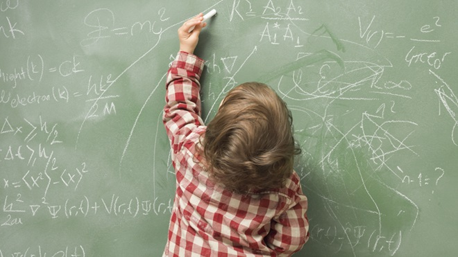 Criança a escrever no quadro com a mão esquerda
