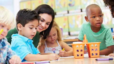 Crianças a fazer um desenho na escola, acompanhadas pela professora.