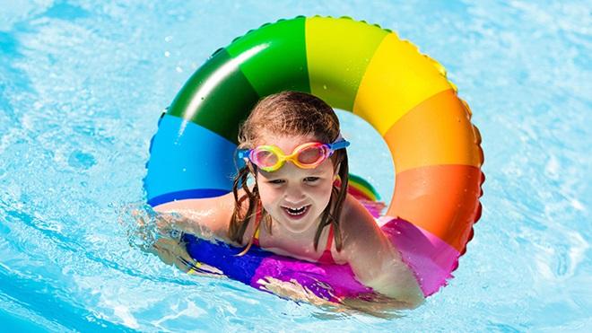 criança na piscina a nadar com a ajuda de uma bóia