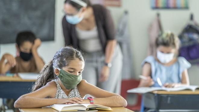 aluna de máscara na sala de aulas da escola com a professora e outros alunos em plano de fundo