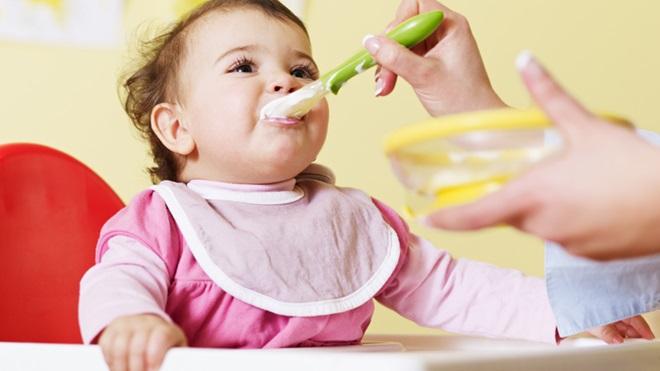 bebé sentada na cadeira de refeição a comer papa com a ajuda da mãe