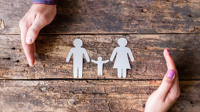 família em papel e duas mãos