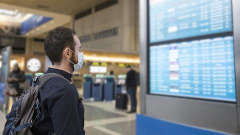 passageiro a ver informações de voo no aeroporto
