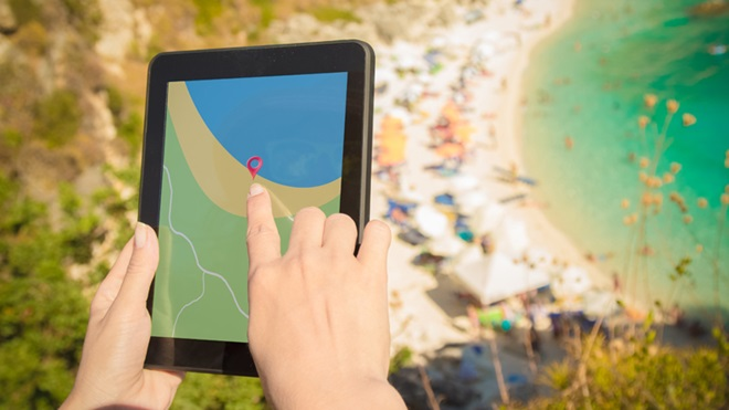 Mulher a pesquisar uma praia num tablet, com um areal e o mar em fundo