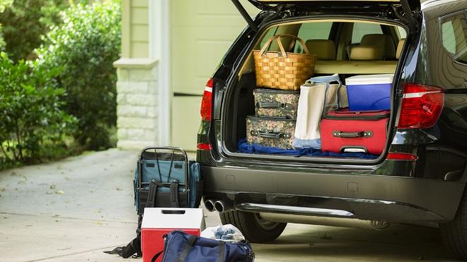 Bagageira de carro aberta cheia de malas de viagem