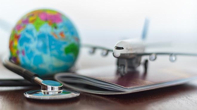 avião, globo e estetoscópio numa mesa