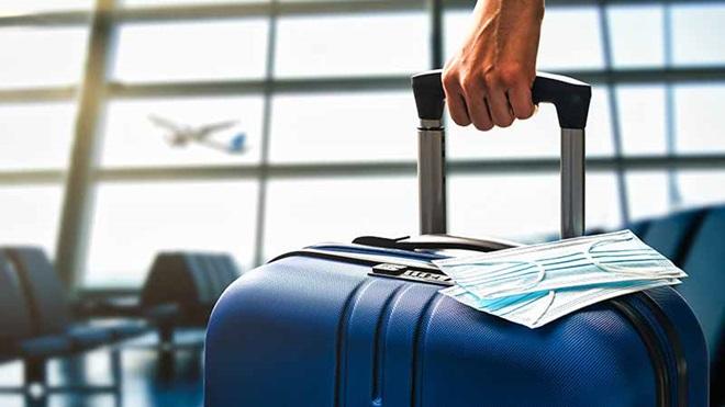 pessoa no aeroporto a puxar uma mala de viagem