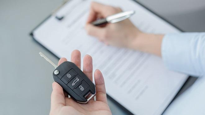 mão esquerda segura chave de rent a car enquanto a direita preenche contrato