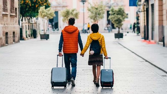 casal de mão dada e de costas com uma mala de viagem cada um