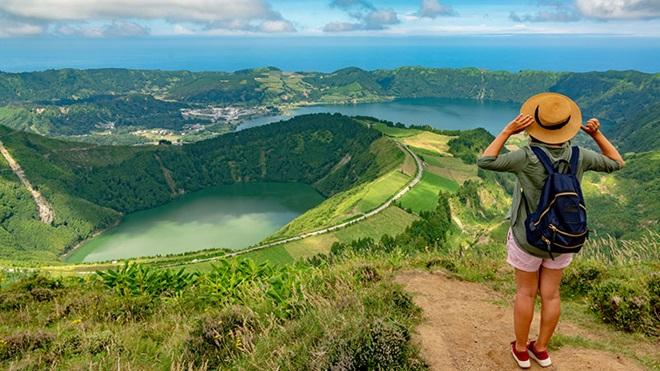 Turista com chapéu e mochila nos Açores a observar a Lagoa das Sete Cidades