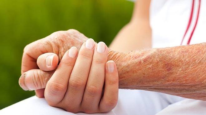 Duas pessoas dão as mãos para decidir sobre o testamento vital