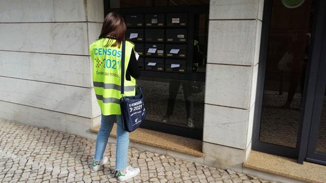 Recenseadora do census 2021 em frente às caixas de correio de um prédio