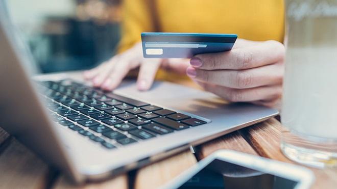 mulher com cartão de crédito ao computador