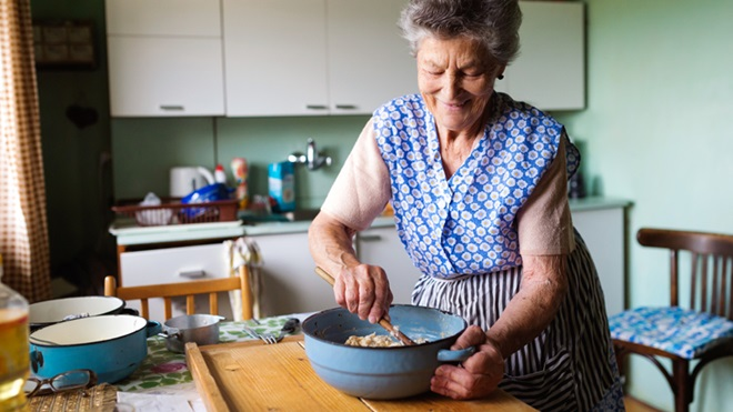 Senhora a preparar comida numa tigela, em cima da mesa da cozinha