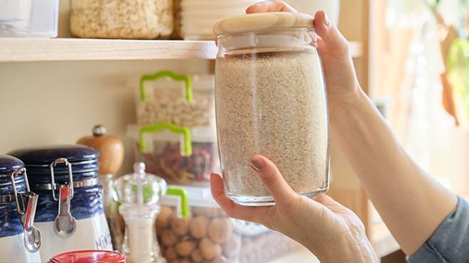 mulher a segurar frasco de arroz junto à despensa na cozinha