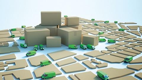 Caixas de cartão dispostas de modo a parecer uma cidade, com camiões e carrinhas de entrega de mercadorias nas estradas