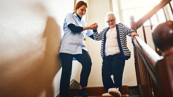 funcionária a ajudar idosa a descer escadas