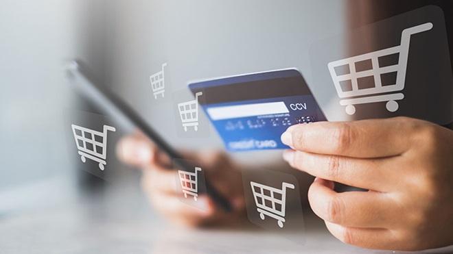 mãos de mulher com telemóvel e cartão de crédito para fazer compras online