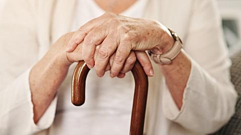 Senhora idosa, vestida de branco, com as mãos cruzadas sobre uma bengala de madeira