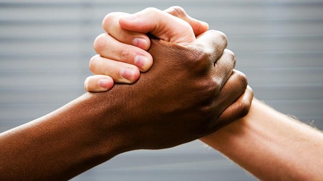 cumprimento entre uma mão de pele branca e outra negra