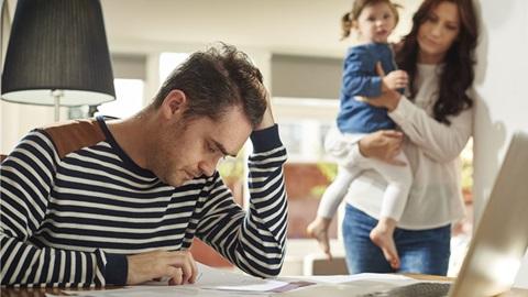 Homem com ar angustiado, em grande plano, e mulher com criança ao colo, em segundo plano. Ambiente doméstico.