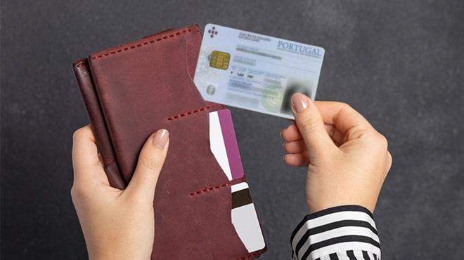 Mãos de muher a colocarem o cartão de cidadão numa carteira com documentos