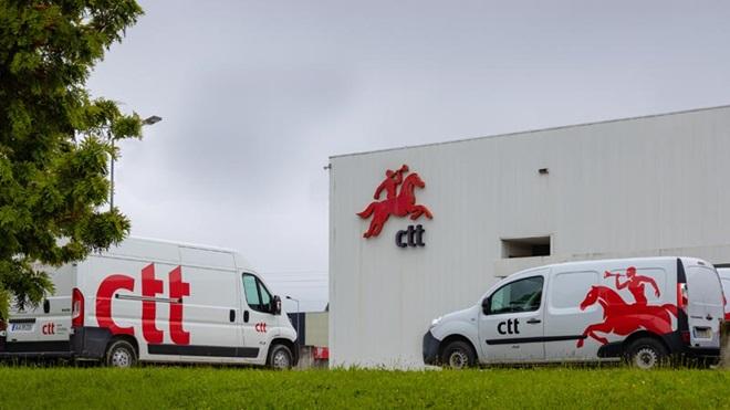 carrinhas de distribuição dos correios em frente a um centro dos CTT