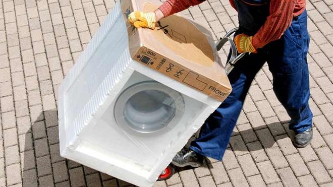 Homem a transportar uma máquina de lavar roupa