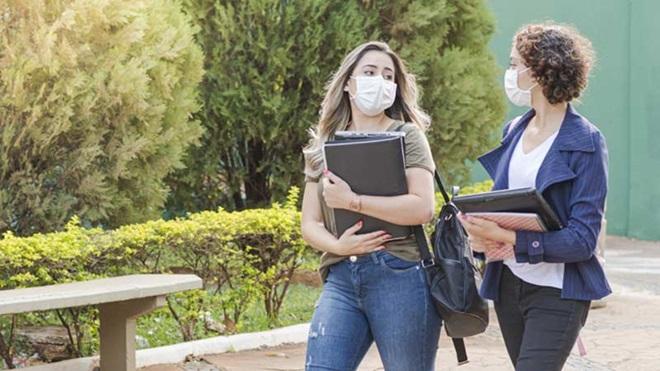duas estudantes com máscara e pastas nos braços a caminho da universidade