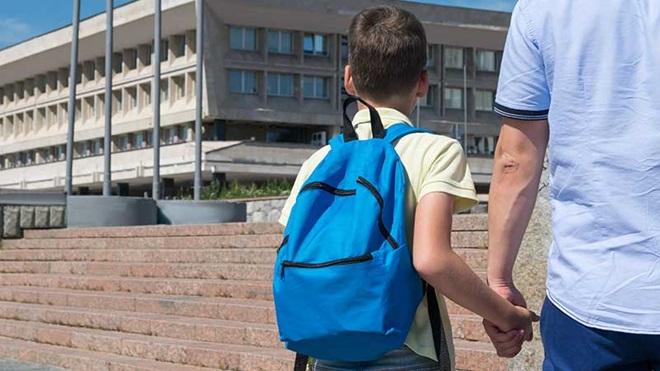 Criança com mochila a caminho da escola de mão dada com o pai