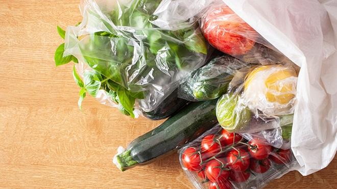saco com vários legumes e fruta embalados com plástico