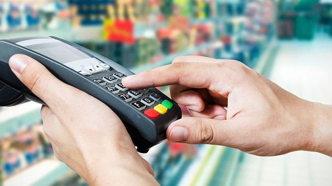 Homem a pagar as compras do supermercado com cartão multibanco