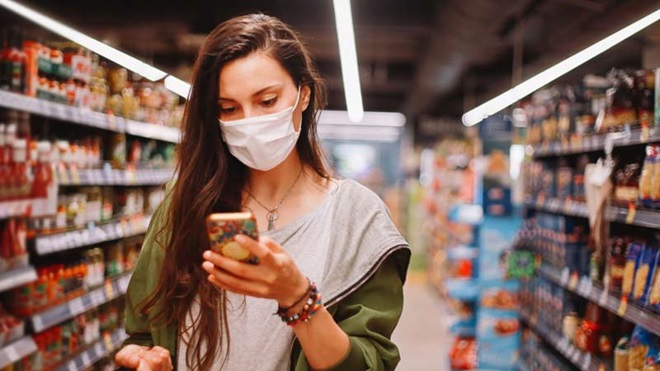 Rapariga usa aplicação no telemóvel para ter desconto no supermercado