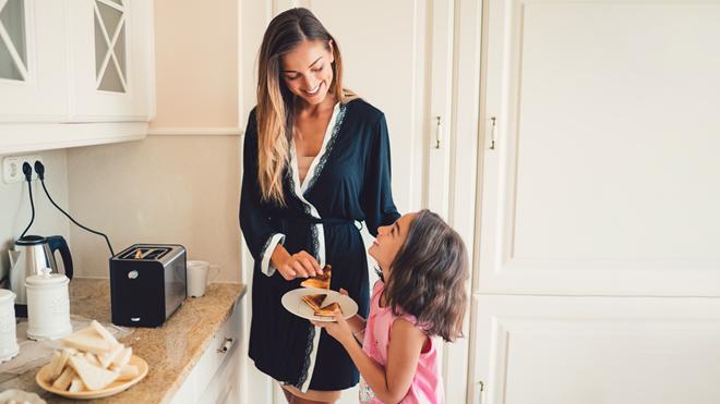 Mãe e filha a torrar pão na torradeira