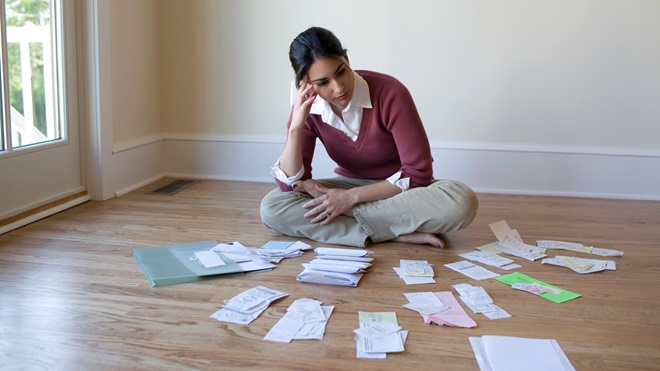 Mulher sentada no chão organiza faturas em papel para preencher a declaração de IRSC