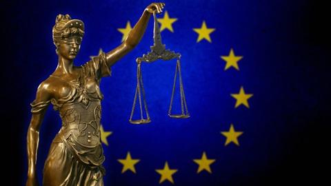 Estátua de bronze com balança na mão e símbolo da União Europeia como pano de fundo