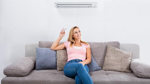 mulher sentada no sofá de casa a regular a temperatura do ar condicionado