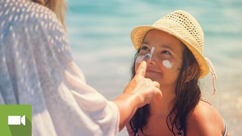 mãe a aplicar protetor solar na filha
