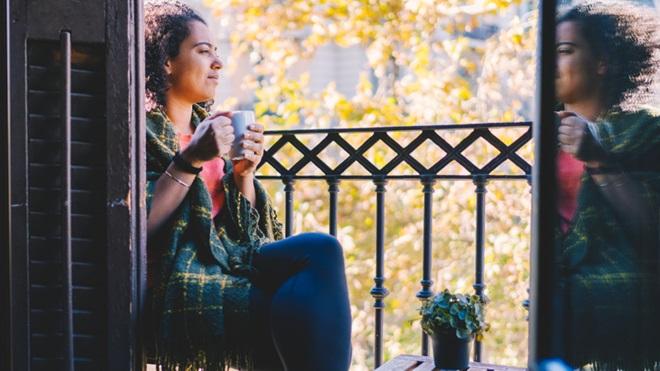 mulher em isolamento profilático em casa, a olhar pela varanda com uma caneca de chá na mão