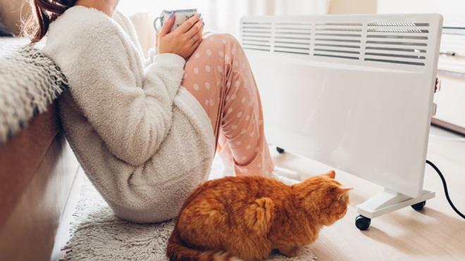 Pessoa com os pés estendidos em cima de um radiador de parede. Os pés têm meias calçadas. Ao lado há um móvel, em cima do qual está uma caneca de chá.