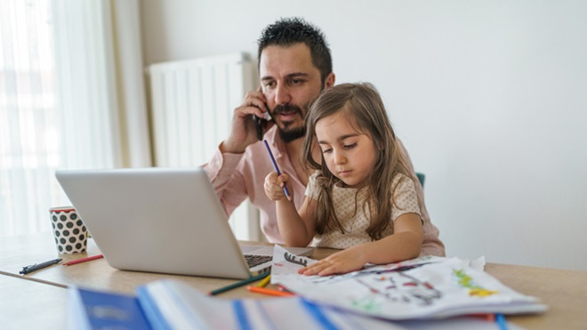 pai em teletrabalho na sala de casa, com um portátil em cima da mesa e a falar ao telemóvel, enquanto a filha está no seu colo a pintar.