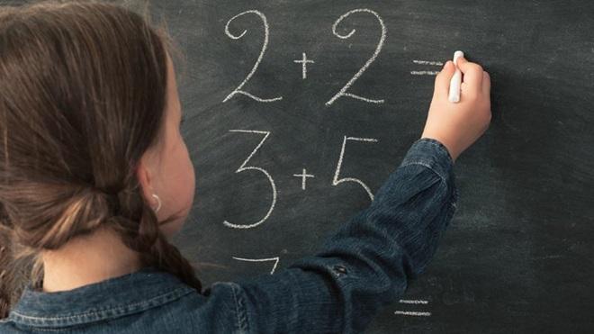rapariga a fazer contas num quadro da escola