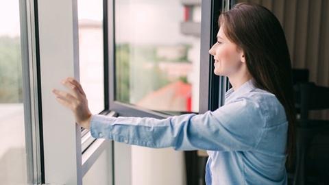 mulher a abrir a janela para refrescar a casa