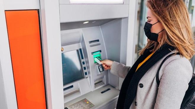 mulher com máscara social no rosto, a levantar dinheiro num caixa multibanco