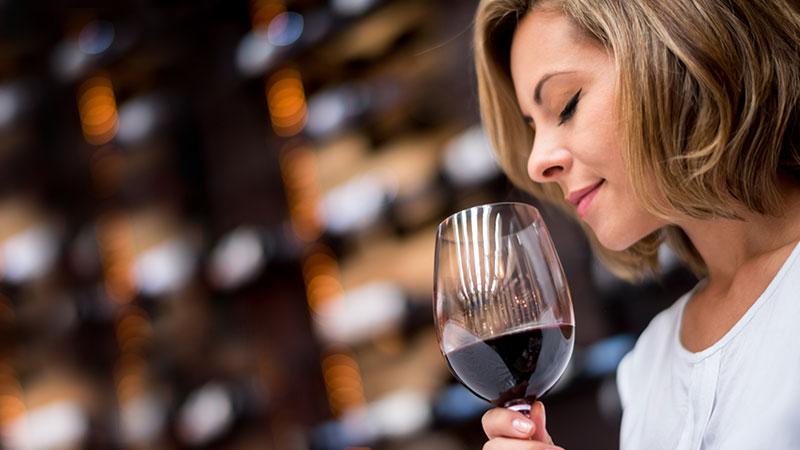 mulher a beber um copo de vinho tinto