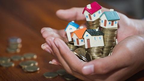 casas pequenas e moedas na mão de uma pessoa
