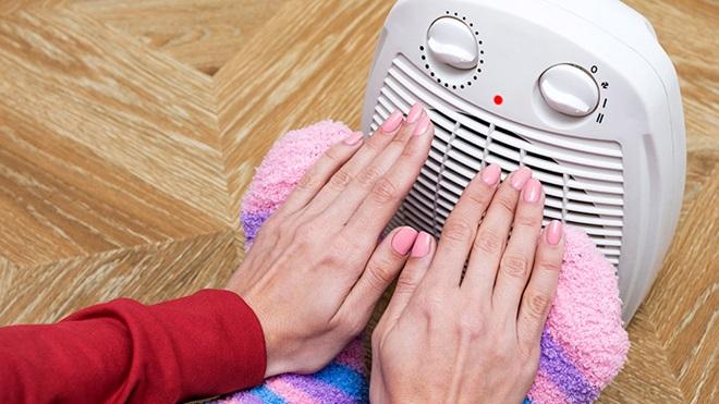 mulher a aquecer as mãos e os pés num termoventilador