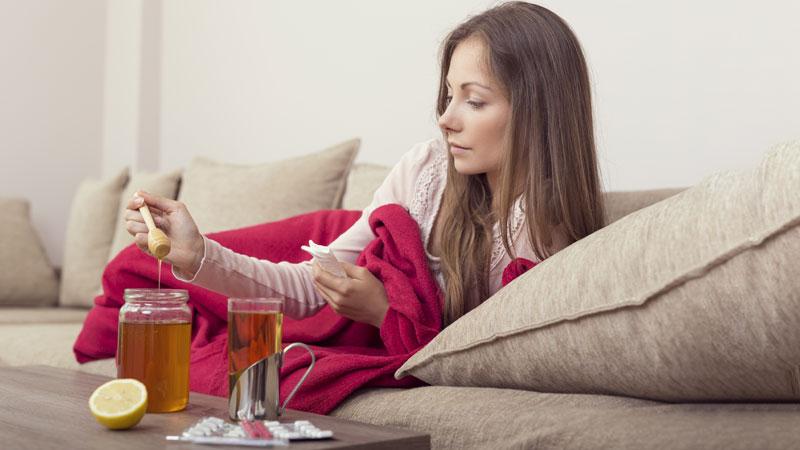 mulher em casa a tomar chá para a gripe